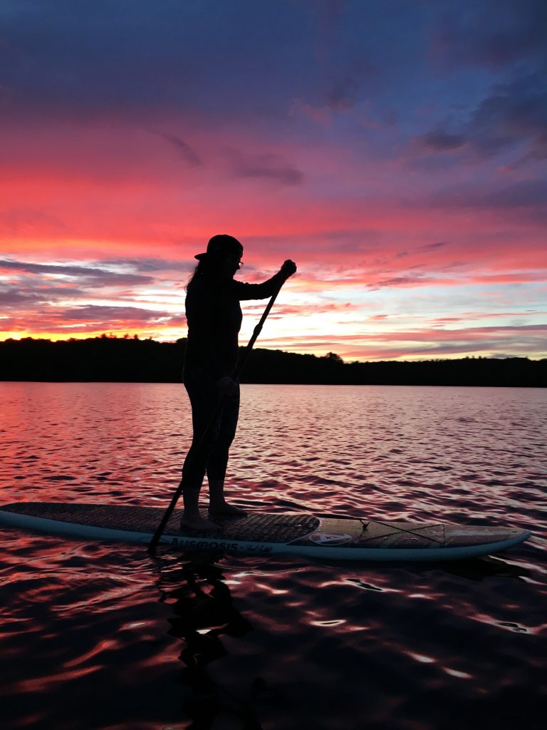 silhouette of a woman with a backwards baseball hat on a paddleboard at sunset with yellow pink and purple skies