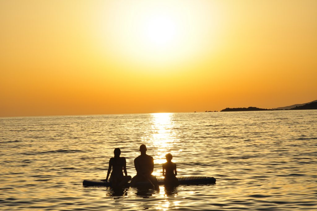 two adults and a child sitting along a paddleboard watching the sun set