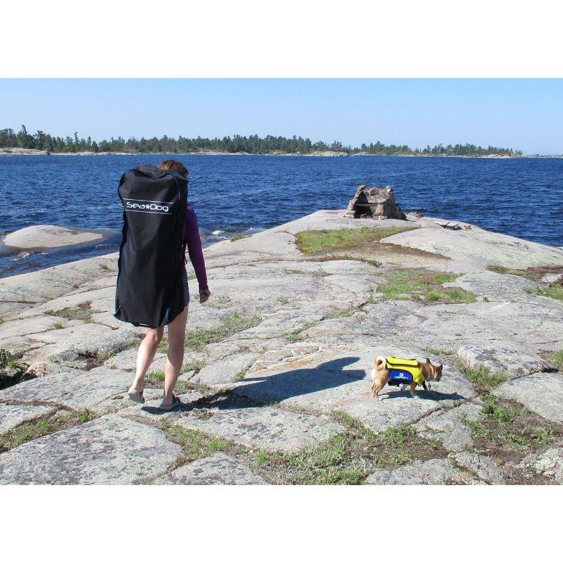 woamn walking toward water with a sea sog backpack on