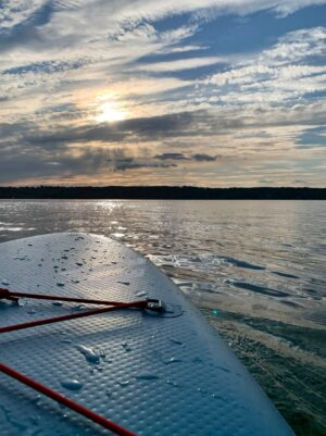 front corner of an iSUP on the water and a sunset